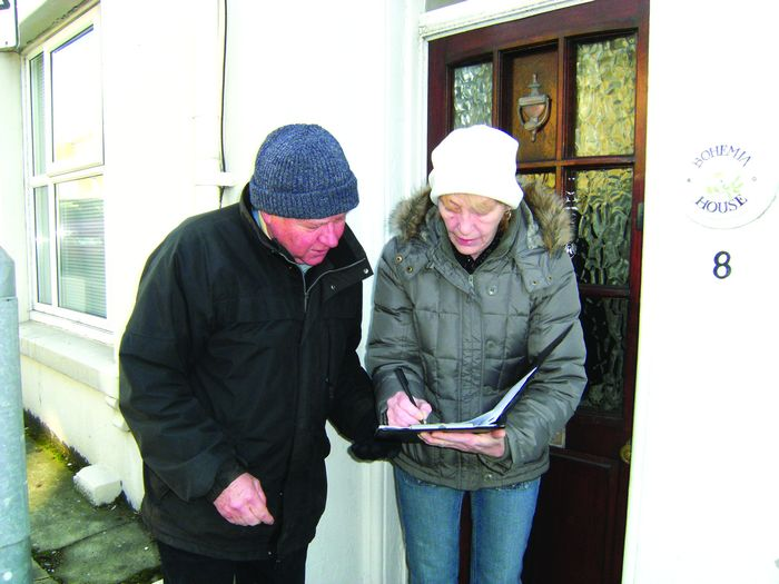 Bill Third, accepting a signature from resident, Mrs J Woodward