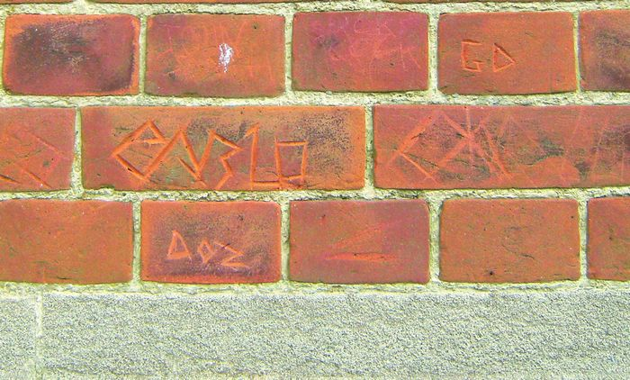 Names scratched into brickwork