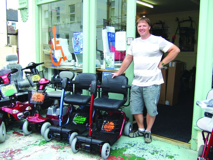 Alan Phillips outside his Tower Rd showroom with just a few of his many scooters.