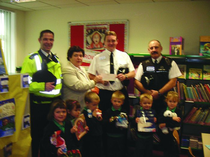 St Pauls head, Pat Lock accepting cheque from Chief Insp Blaker. Bohemia street bobby Andy Hubbard attends.