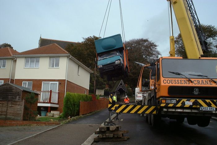 The crane makes small work of the van.